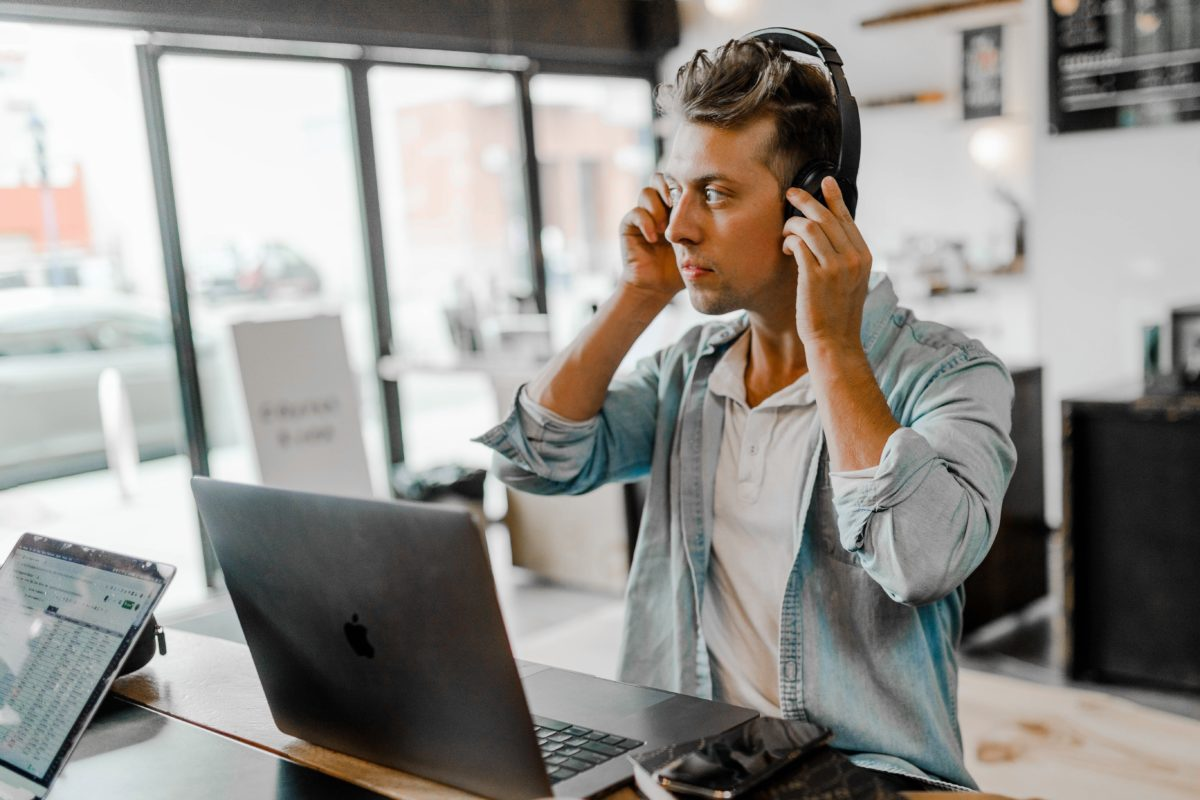 A person putting on a headset listening to music from a laptop